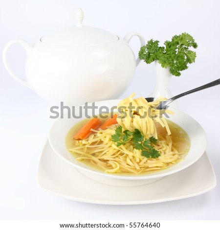 Chicken soup with macaroni and carrots decorated with parsley on a plate, some of it on a spoon ,  with soup tureen and parsley in the background - stock photo