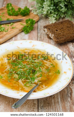 chicken soup with noodles and carrots with fresh herbs on the plate, vertical - stock photo