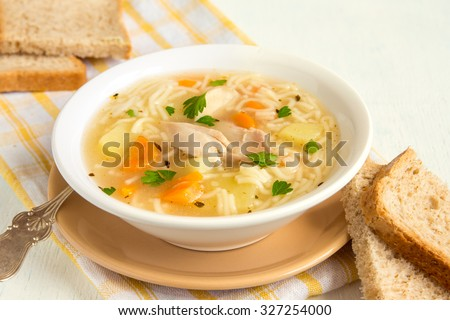 Chicken soup with noodles and vegetables in white bowl - stock photo