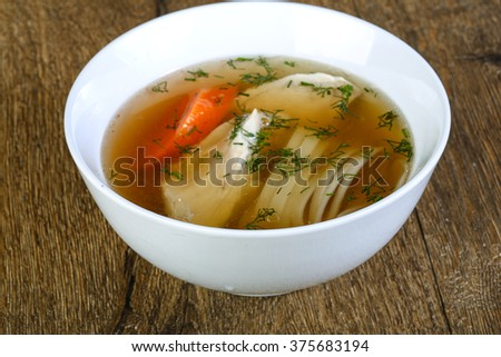 Chicken soup with noodles on the wood background