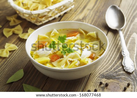 Chicken soup with pasta Farfalle in the bowl on the table - stock photo