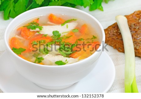 Chicken soup with vegetables in white bowl on a table - stock photo