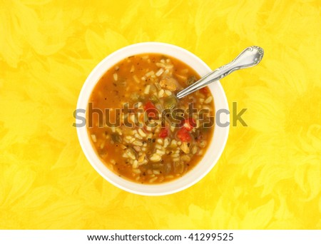Chicken soup with vegetables in white bowl with spoon