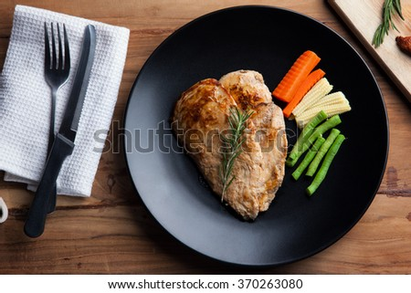 chicken steak with rosemary and vegetable on black plate - stock photo