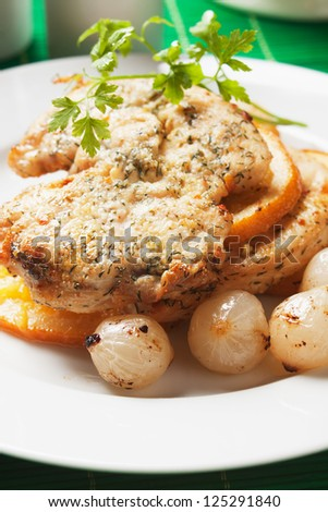 Chicken steak with slices of fried orange and onion