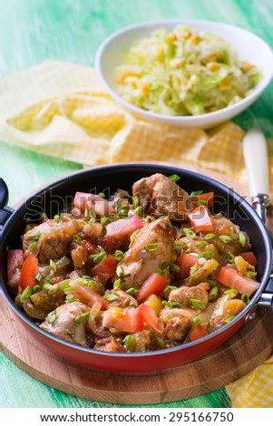Chicken stew with onion, pepper ant tomato, selective focus, green background, top view
