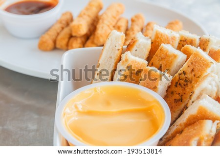 Chicken stick and bread stick with sauce on white plate. - stock photo
