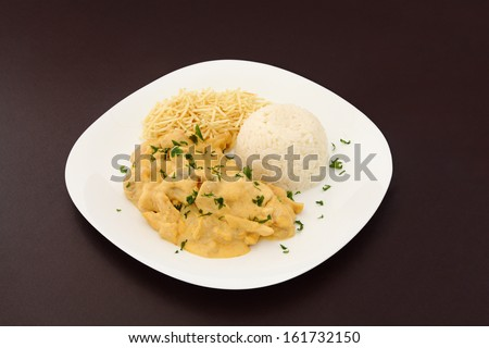 Chicken stroganoff dish with shoestring potato and rice on brown leather background. - stock photo