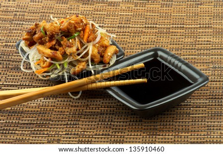 Chicken Teriyaki with Chinese Glass Noodles and Soy Sauce in Black Square Shape Bowls with Pair of Chopsticks on Straw mat background - stock photo
