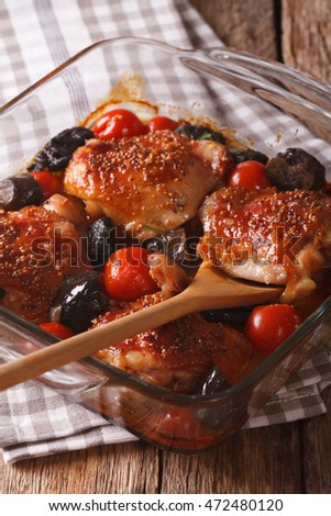chicken thigh baked with tomatoes and cep mushrooms close up in baking dish on the table. vertical