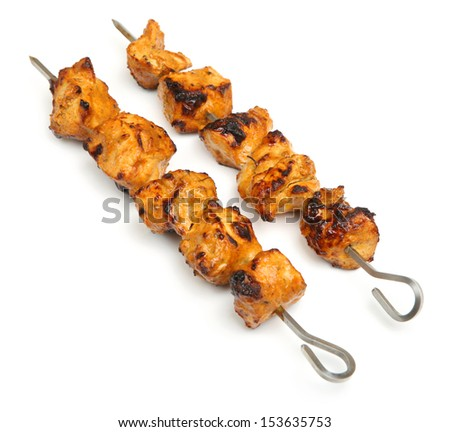 Chicken tikka kebabs on metal skewers.