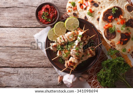 Chicken tikka on skewers, naan flat bread and chutney. horizontal top view