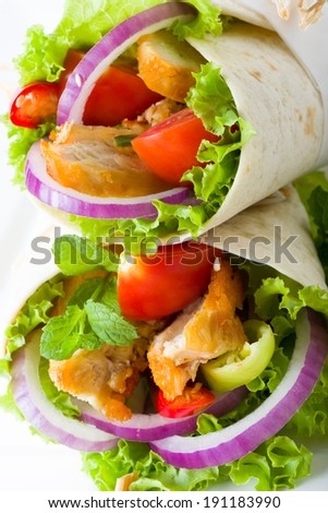 Chicken tortilla with fresh healthy salad ingredients including lettuce, onion, tomato and herb, close up view of two on top of each others - stock photo