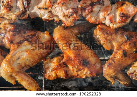 Chicken wings  and Juicy roasted  kebabs and  on the barbecue - stock photo