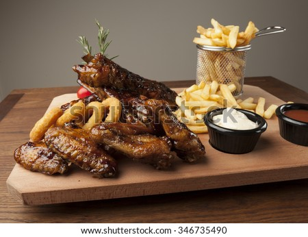 chicken wings and ribs with fries on wooden table - stock photo