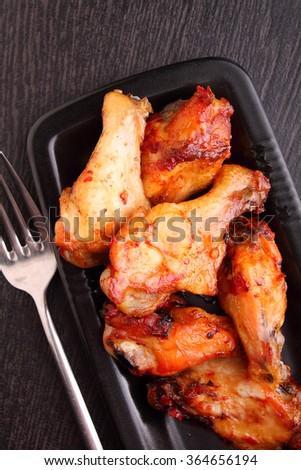 chicken wings baked in tomato sauce on a black plate