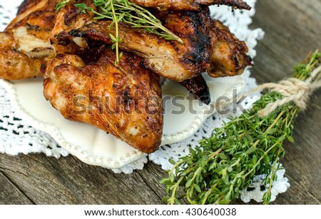 Chicken wings fried with thyme on a plate on a knitted cloth on the old table in rustic style. - stock photo