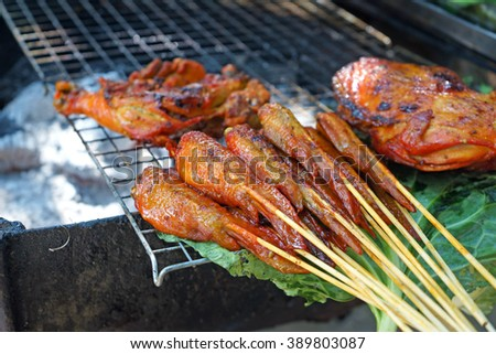 Chicken wings on barbecue grill with sauce.Popular in Thai