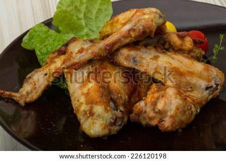Chicken wings roasted - served with salad leaves, thyme and tomato