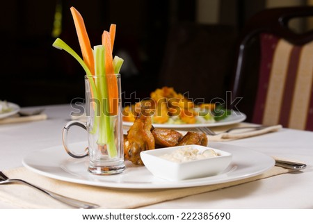 Chicken Wings with Carrots and Celery and Dip on Restaurant Table - stock photo