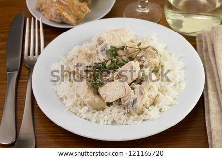 chicken with champignons, sceams and boiled rice and glass of wine