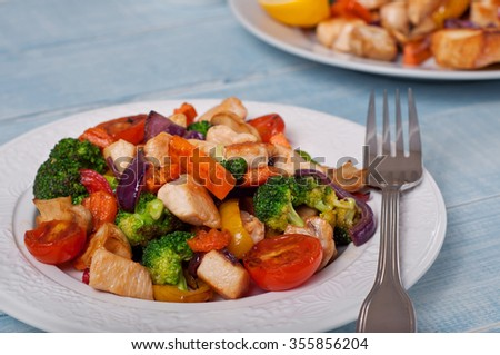 Chicken with grilled vegetables on white plate on wooden table closeup