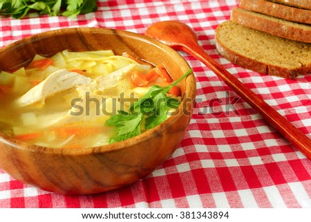 chicken with noodles soup in a wooden bowl. On a red tablecloth into the cell. Dark bread.
