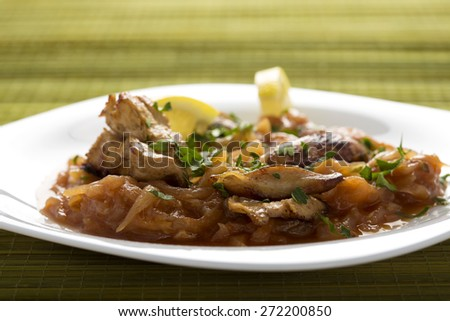 Chicken with onion and lemon on a white plate - stock photo