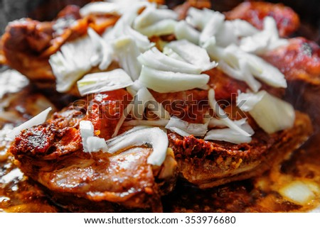 Chicken with onion and spice on frying pan - stock photo