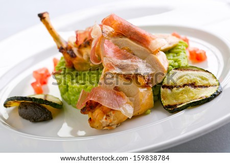 chicken with parma ham and risotto - stock photo