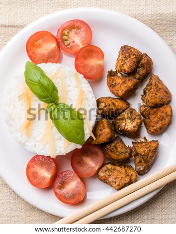 chicken with rice and tomatoes on white plate