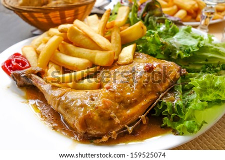 Chicken with sauce and golden French fries potatoes  - stock photo