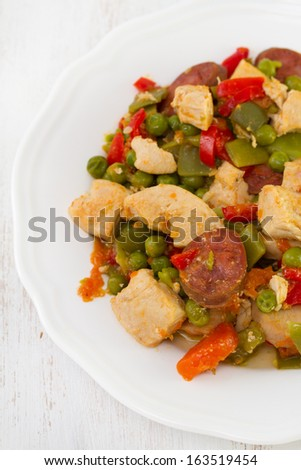 chicken with sausages and vegetables on plate