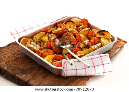 Chicken with vegetables on a baking tray as a studio shot - stock photo