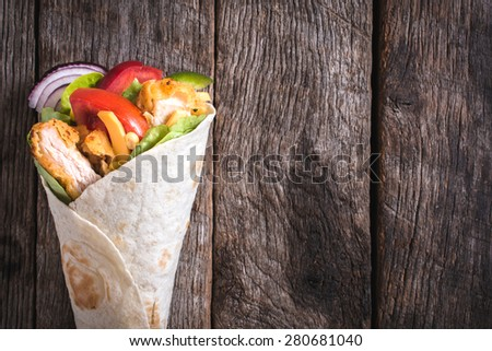 Chicken wrap sandwich on wooden background with blank space - stock photo