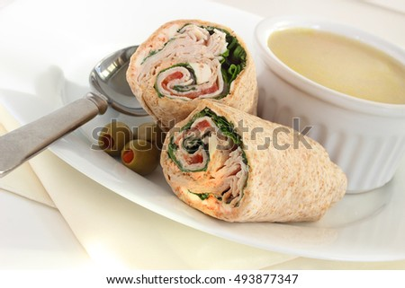 Chicken wrap served with savory green lentil soup gently seasoned with cumin and turmeric, a healthy lunch or dinner for one