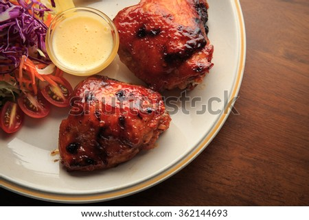Chickens fried steak with vegetables salad on white dish and wooden background