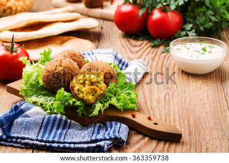 Chickpea falafel balls on a wooden desk with vegetables - stock photo