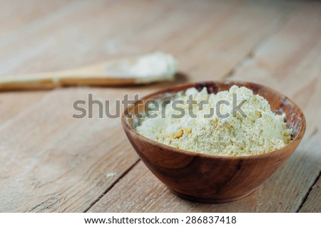 Chickpea flour in old wooden bowl on wooden background