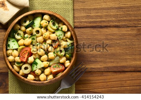Chickpea salad with green olives, cucumber, cherry tomato and parsley, served in wooden bowl, pita bread pieces on the side, photographed overhead with natural light