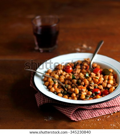 Chickpea stew with roasted cherry tomatoes, sweet bell pepper, chicken garnished with fresh chopped parsley and peppercorns in a plate with a glass of wine on a wooden rustic table, selective focus - stock photo