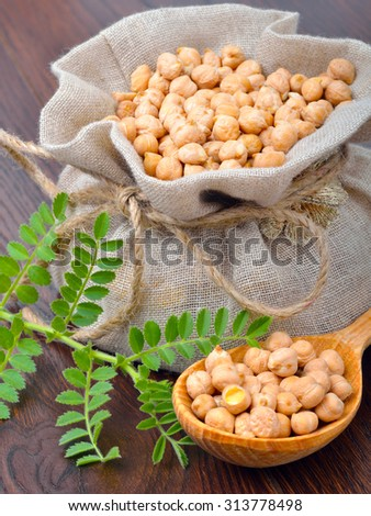 Chickpea varieties in a burlap bag with green sprouts on a wooden background - stock photo