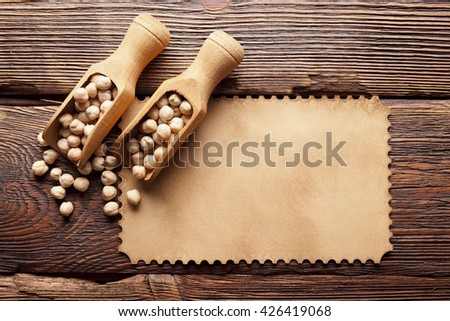 Chickpeas in wooden spoon and blank paper label - stock photo