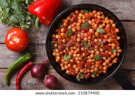 Chickpeas with chorizo ??in a pan close-up and with the ingredients on the table horizontal top view   - stock photo