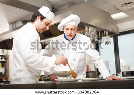 Chief chef watching his assistant garnishing a dish - stock photo
