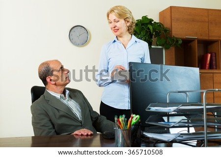 Chief giving new task to mature female secretary