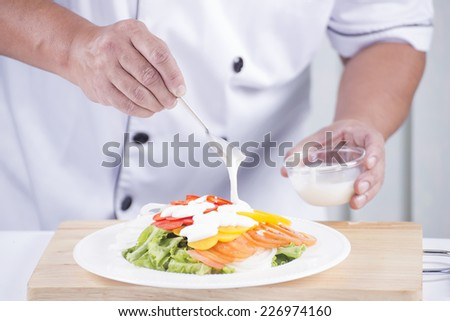 Chief putting salad dressing / Making Salad concept