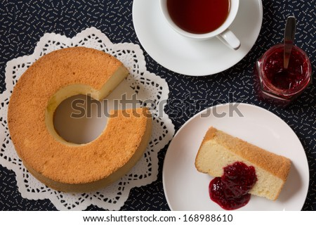 Chiffon cake with characteristic hole in the center from an ungreased tube pan. The cake is made with vegetable oil, eggs, sugar, flour, and flavorings. Served with raspberry jam, and a cup of tea. - stock photo