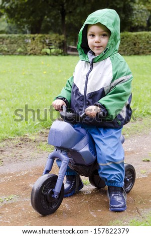 Child , a toddler boy, riding a toy bike in park on rainy day.