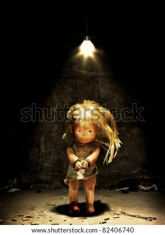 Child abuse - a doll in a dark room with hands tied and mouth sealed
